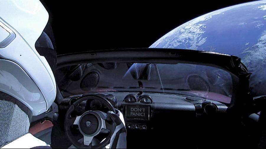 Les images retransmises en direct sont suivies par des millions de spectateurs. Sur le tableau de bord : « Don't panic ! » Une référence au « Guide du voyageur galactique » de Douglas Adams (1978).