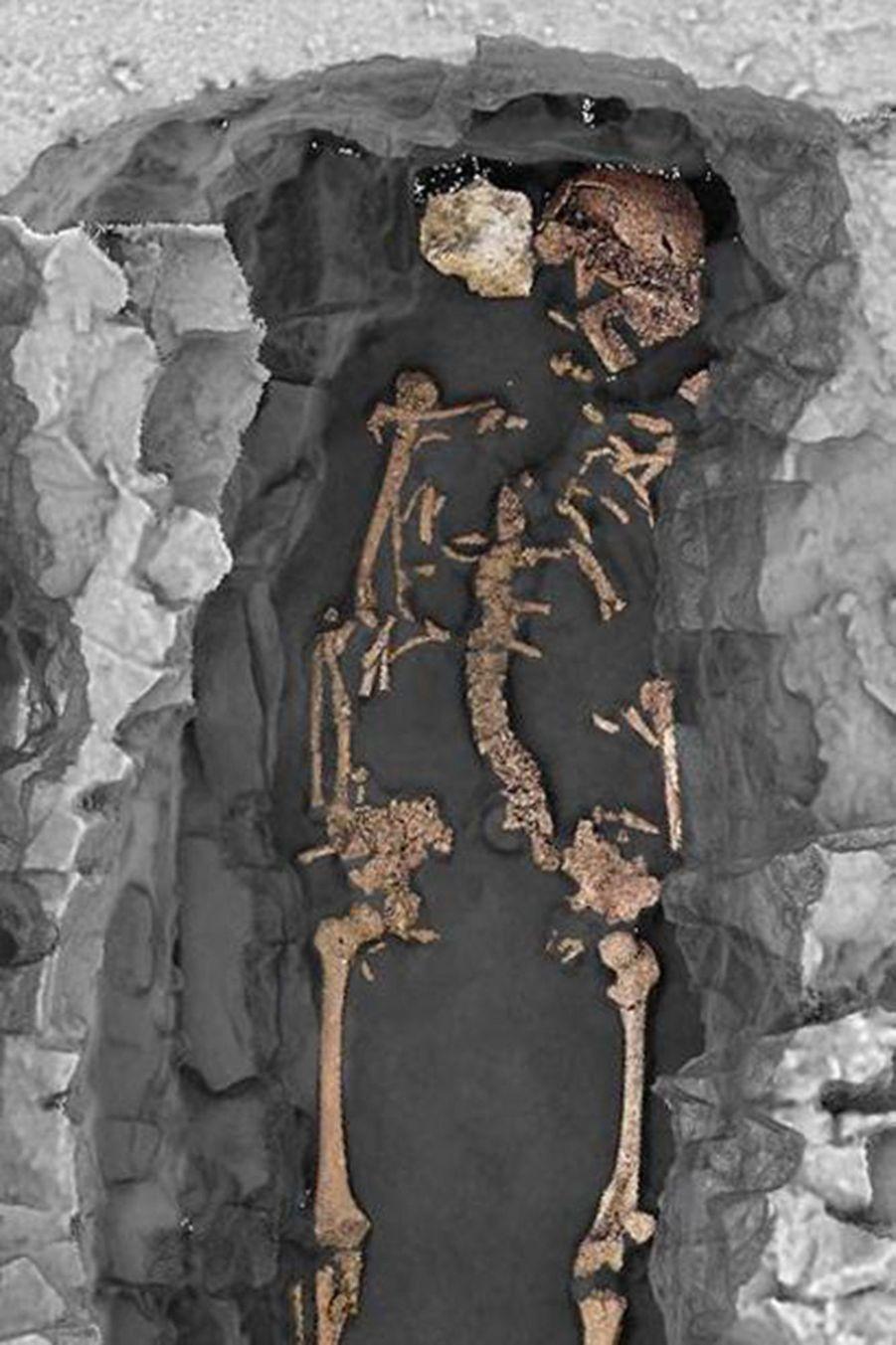 Vue zénithale 3D d'une sépulture individuelle. L'individu est un adulte féminin, inhumé sur le dos avec les membres supérieurs en extension le long du corps et selon une orientation ouest-est. Deux pierres encadrent le crâne. La décomposition du corps s'est effectuée en espace vide.