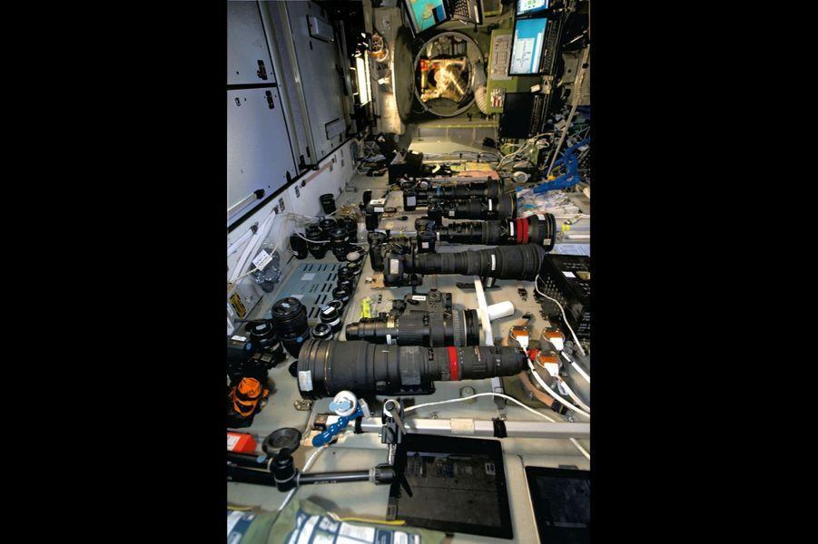 Dans la Station, longue de près de 100 mètres, le matériel photo est soigneusement rangé dans la partie russe : des téléobjectifs longs comme des canons. Au fond, le superhublot à visée verticale et (à dr.) le logiciel de navigation sur l''écran de l''ordinateur