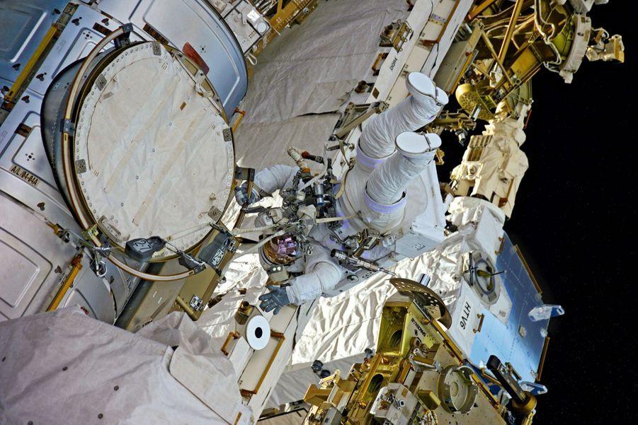 Pendu à la main courante, à la sortie du sas. Dans l'objectif d'Oleg, le cosmonaute russe, le 13 janvier