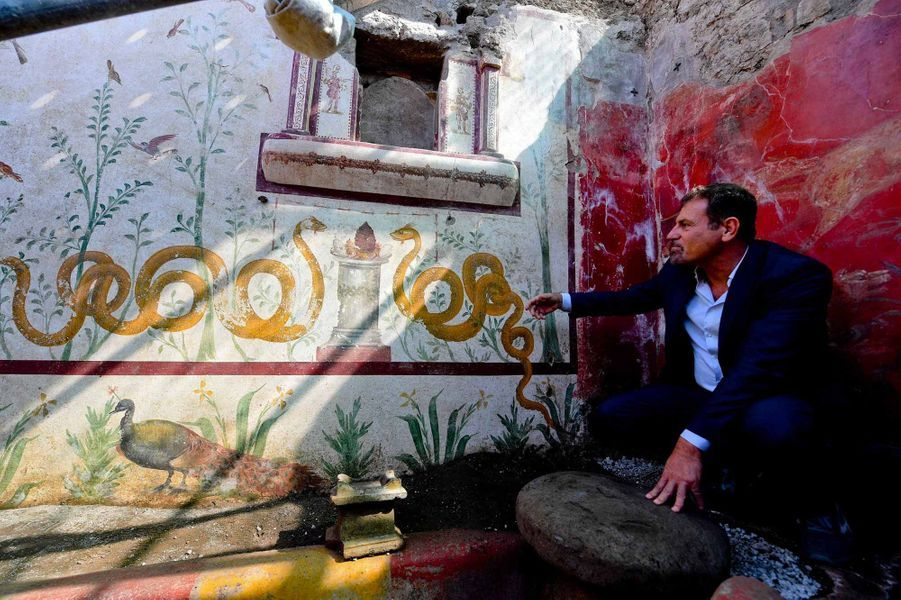 Le responsable du parc archéologique de Pompéi Massimo Osanna se tient devant la fresque murale fraichement mis au jour dans une maison romaine.