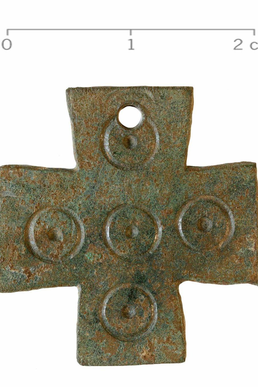 Petite croix en alliage cuivreux, décor en ocelles.