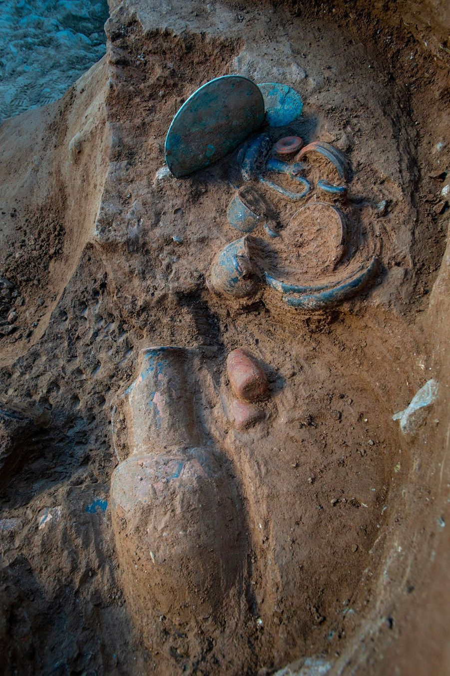 Poteries, objets en bronze et miroir en cours d'exhumation dans une tombe étrusque.