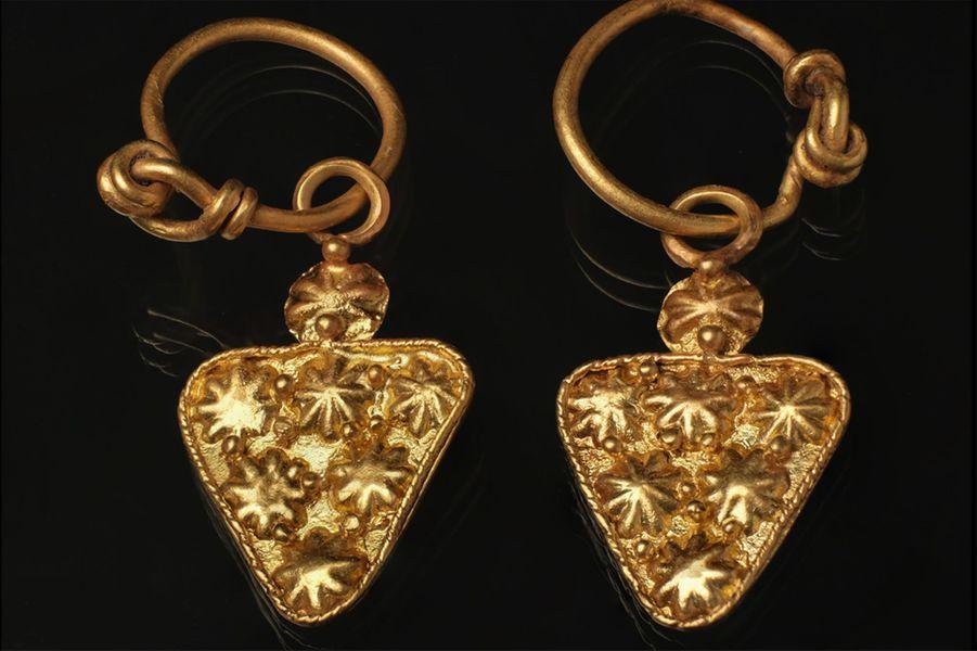 Boucles d'oreilles découvertes dans une sépulture de brique livrant aux pieds du sujet dans un espace quadrangulaire (possiblement un coffret en bois ou une ciste en osier) les éléments d'un collier de perles en verre et deux perles tubulaires en or.