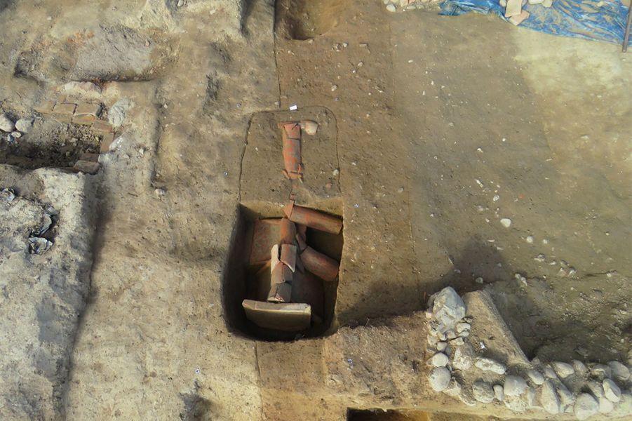 Nécropole d'Aléria – Lamajone. Au centre une tombe à fosse avec couverture detegulaeetimbrexrecoupe le couloir de l'hypogée visible grâce à la couleur plus orangée du sédiment qui la comble.