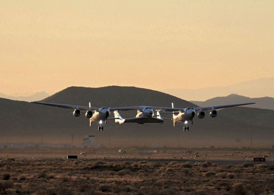 WhiteKnightTwo décolle de l'aéroport californien Mojave Air and Space. Avec 42 mètres d'envergure, c'est le plus gros avion en carbone du monde. La navette SpaceShipTwo est suspendue entre les deux carlingues.