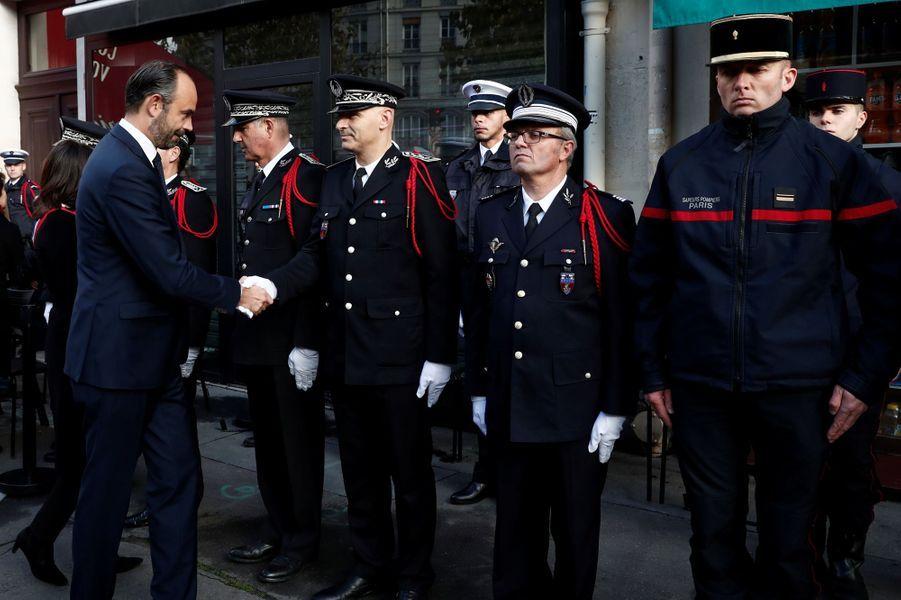 Edouard Philippe salue les forces de l'ordre devant le Comptoir Voltaire.