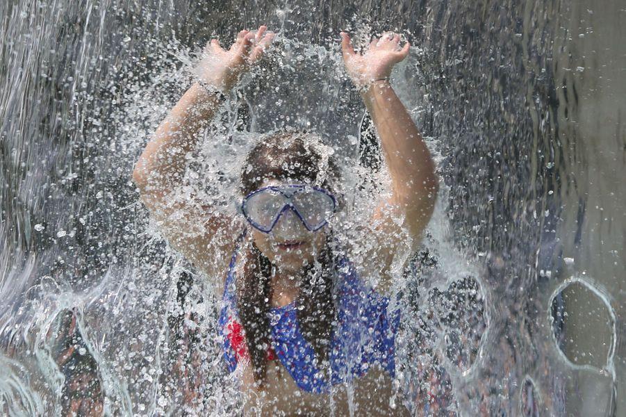 A Bonn (Allemagne), une fillette s'amuse dans une fontaine.
