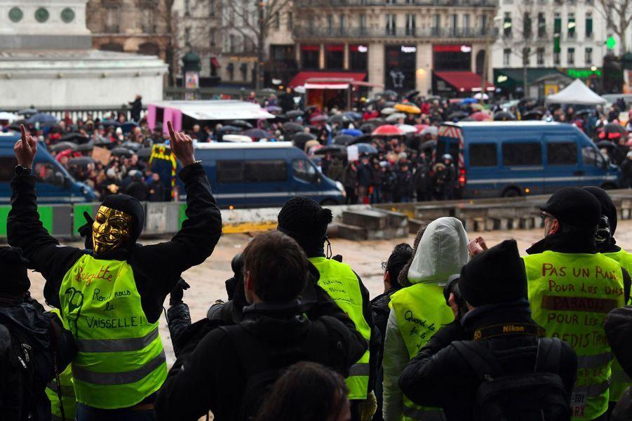 Des «gilets jaunes» interpellent les «foulards rouges» à Paris, dimanche.