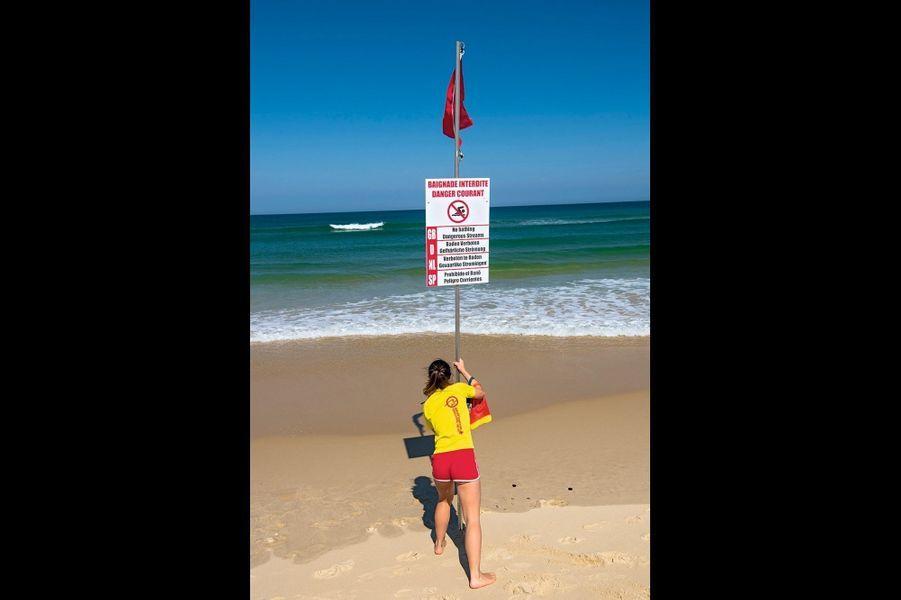 Baignade interdite ! Morgane hisse le drapeau rouge sur la plage de Biscarrosse.