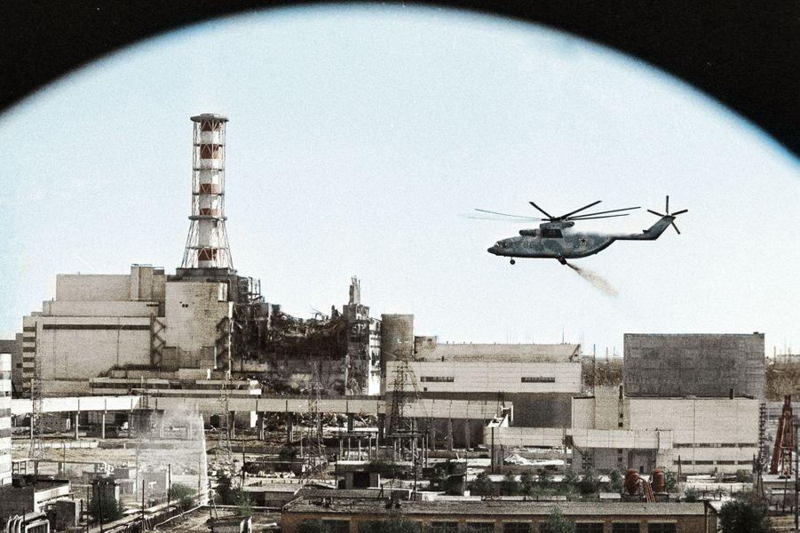 Un hélicoptère de « liquidateurs » soviétiques déverse du sable et de l'argile sur le réacteur en fusion de la centrale de Tchernobyl, en 1986.