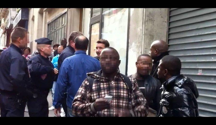 Olivier Besancenot est repoussé, sans violence, contre le mur de l'immeuble pendant que d'autres policiers embarquent le vendeur à la sauvette.