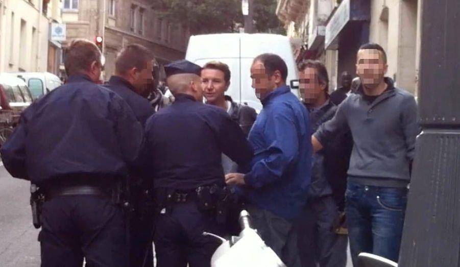 La scène a attiré un grand nombre d'habitants du quartier. Le dirigeant du NPA a le visage tendu par la colère.