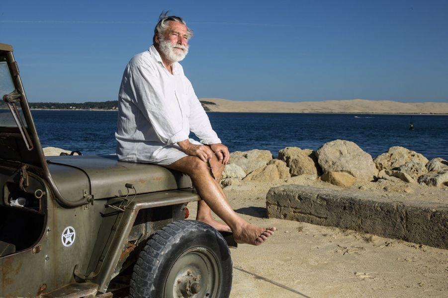 Benoît Bartherotte pose devant sa digue, construite avec ses économies, à la pointe du Cap Ferret.