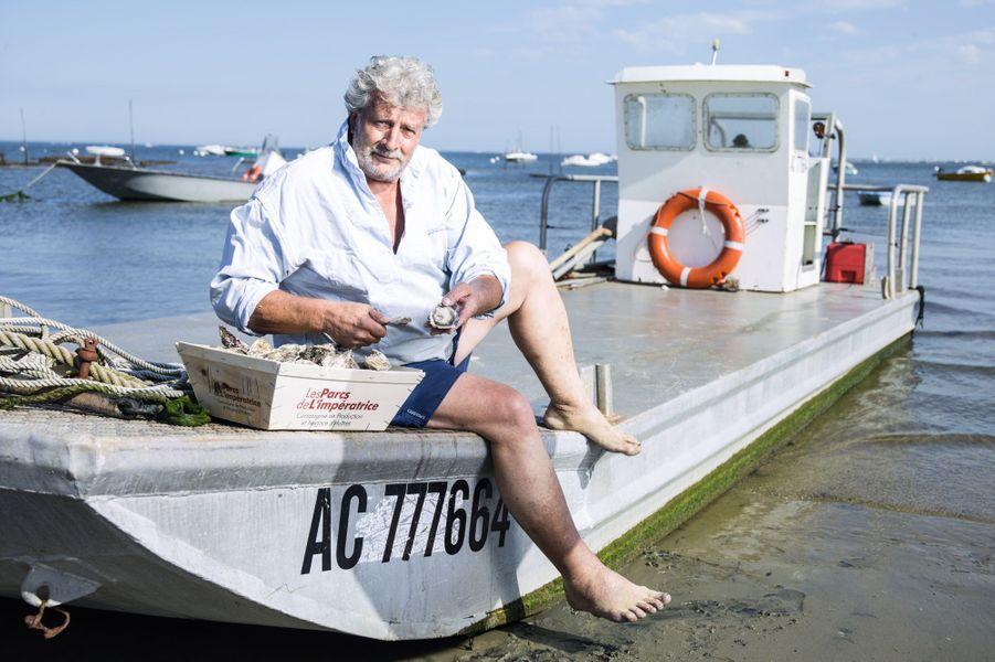 Joël Dupuch célèbre ostréiculteur depuis le film «Les Petits Mouchoirs», sur son chaland avec une bourriche de ses huîtres, Les Parcs de L'impératrice.