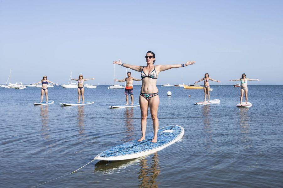 La Cabane de la glisse organise des séances de Yoga paddle sur les eaux calmes du bassin d'Arcachon. Devant, Emilie Daillere, professeur de yoga et fondatrice de Yoga Esprit Surf.