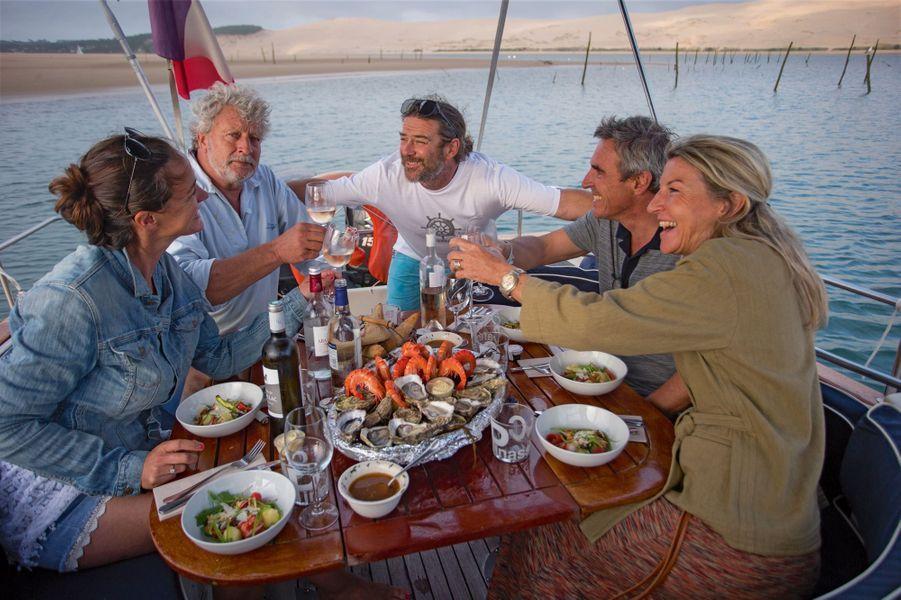 Pinasse Café, le restaurant tenu par Alexandra et Laurent Tournier (à droite) et Cyril, capitaine du «Cap 114» (au centre) organisent des pique-niques de luxe sur l'eau. A gauche, leurs invités : Elise et son mari,Joël Dupuch.
