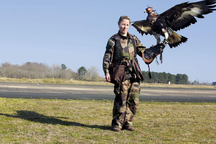 Une militaire, agent de la prévention animalière, avec l'un des quatre premiers aigles royaux accueillis sur la base.
