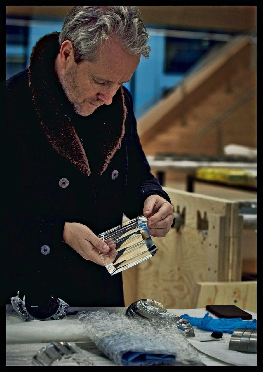 Le designer Ronan Bouroullec examine la finition des maillons en cristal qui, mis bout à bout, formeront des tubes longs de 12 mètres