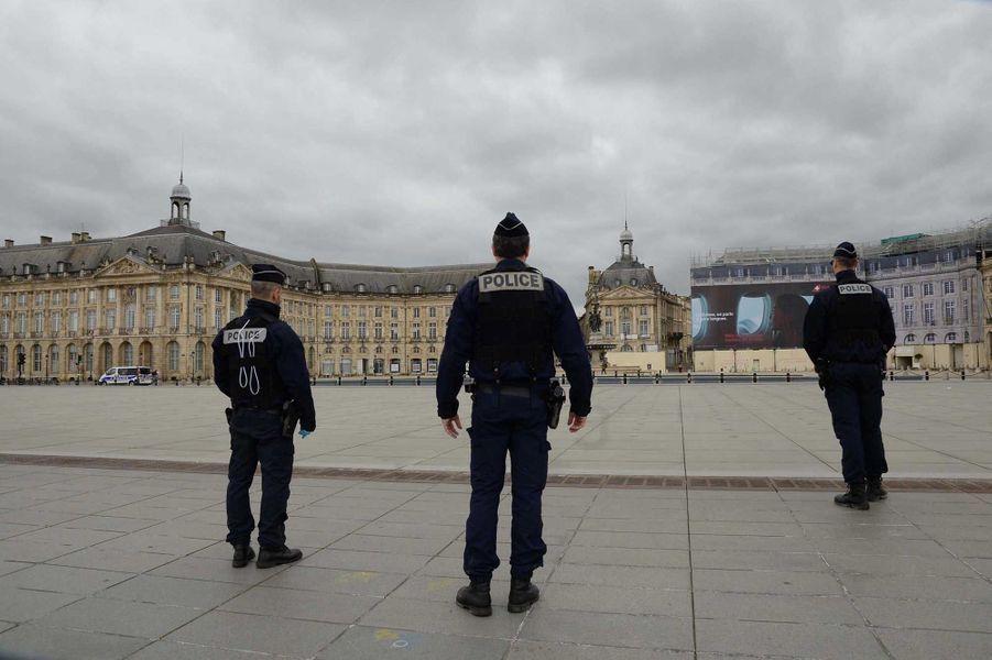 Des policiers devant une place de la Bourse vide, à Bordeaux