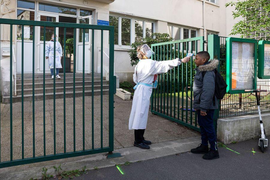 A Versailles, à l'école le village de Montreuil, la directrice prend la température d'un élève.