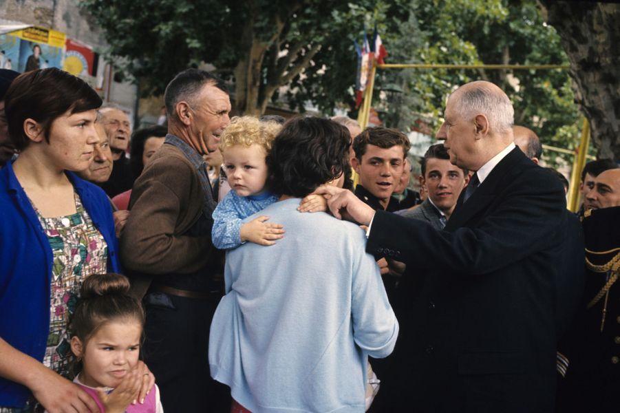 Charles de Gaulle, en costume cravate, salue la foule en tenant la main d'un enfant lors d'une visite officielle dans le sud-est, septembre 1963
