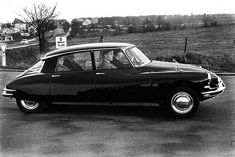 De Gaulle à l'arrière de sa voiture lit le journal