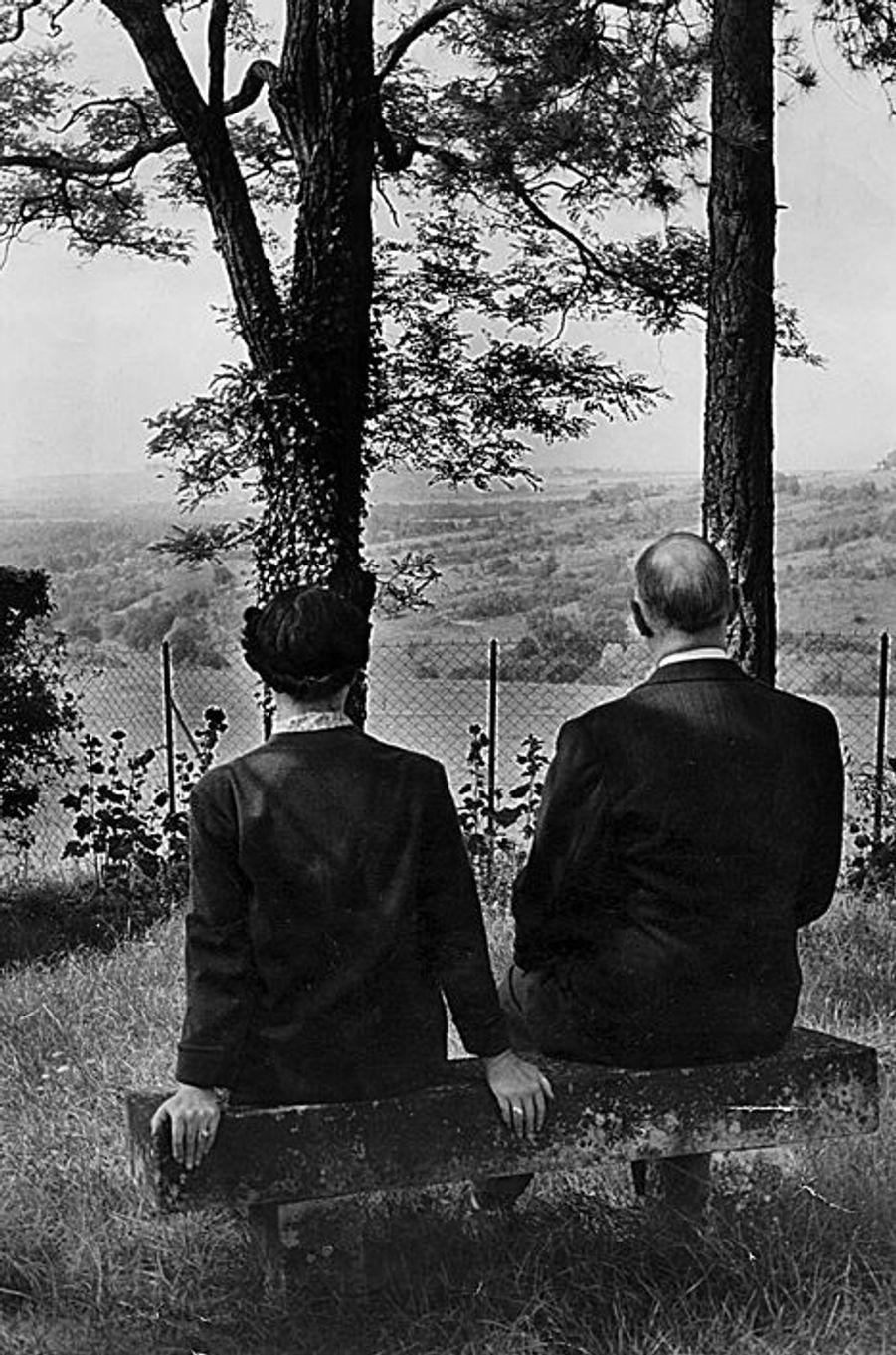 Les deux amoureux sur un banc moussu au fond du parc de leur propriété à Colombey