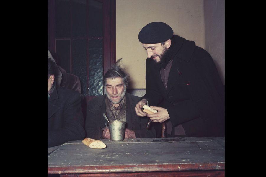 Fondateur de la communauté d'Emmaüs, l'Abbé Pierre est devenu du jour au lendemain l'apôtre des sans-logis.Le matin du 1er février 1954, il lance à la radio un appel en faveur des sans-abris, qui, repris par la radio, la presse et la TV soulève une immense vague de solidarité. Ici l'abbé partageant du pain avec un homme semblant à bout de forces.