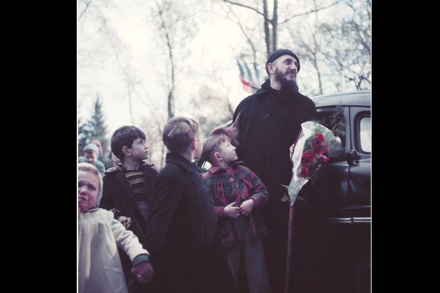 Fondateur de la communauté d'Emmaüs, l'Abbé Pierre est devenu du jour au lendemain l'apôtre des sans-logis.Le matin du 1er février 1954, il lance à la radio un appel en faveur des sans-abris, qui, repris par la radio, la presse et la TV soulève une immense vague de solidarité. Ici, l'abbé en mission, entouré par des enfants.