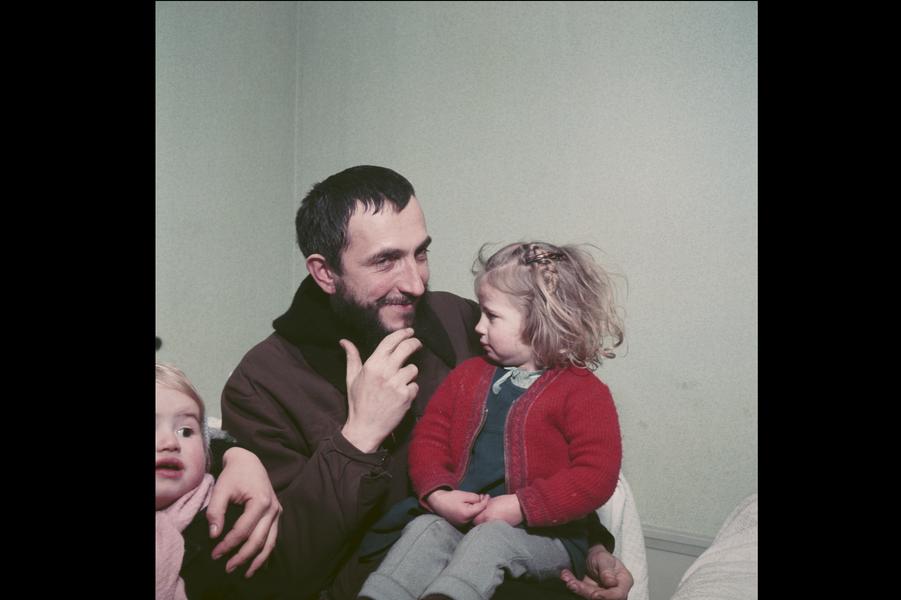 Février 1954 : en visite chez la famille Porte, l'abbé Pierre jouant avec les enfants, la petite Annie blottie contre lui.