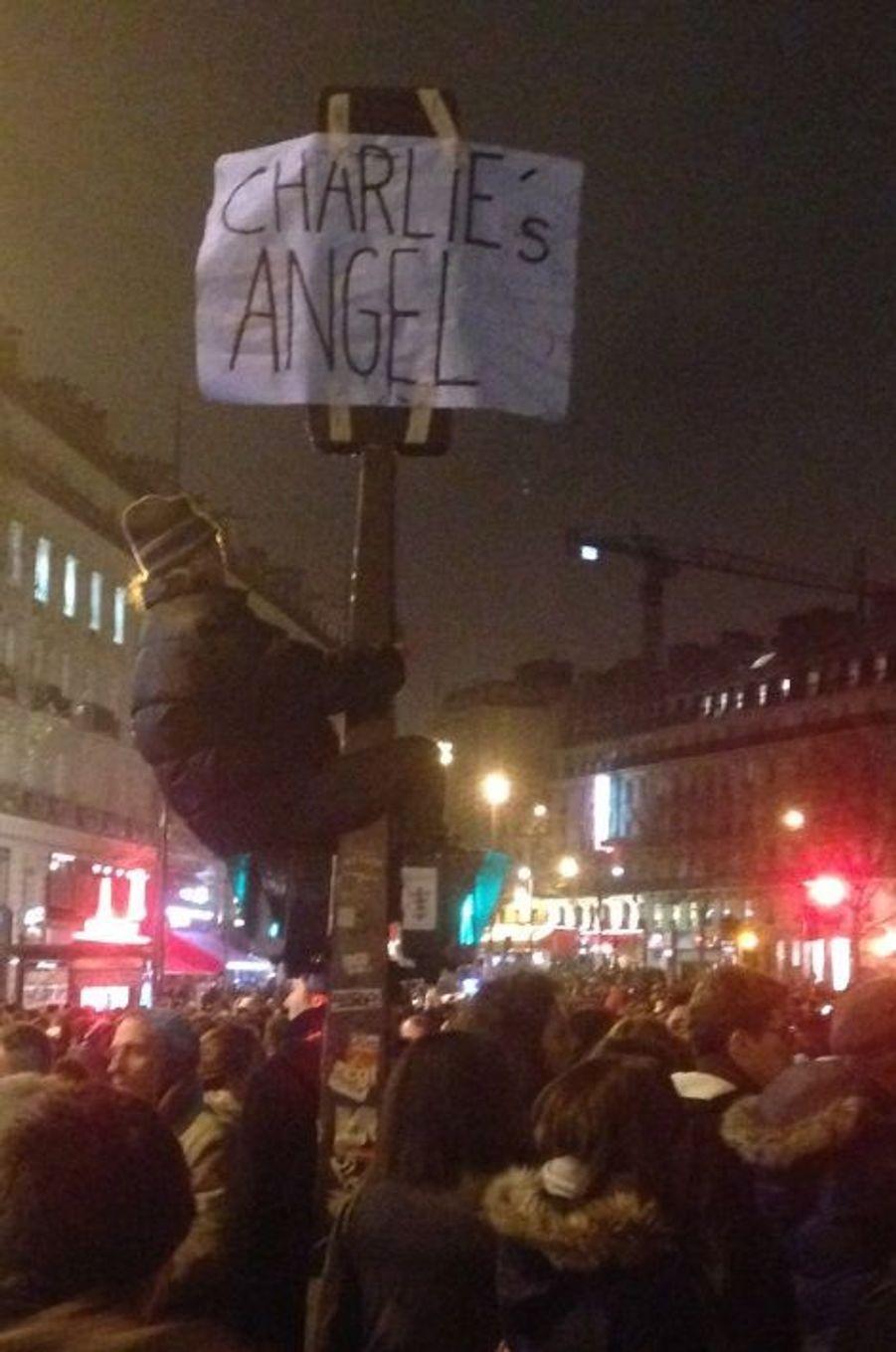"""Beaucoup ont voulu retrouver l'esprit potache des journalistes de Charlie Hebdo, comme ce manifestant qui affiche """"les Anges de Charlie"""" en hommage aux victimes."""