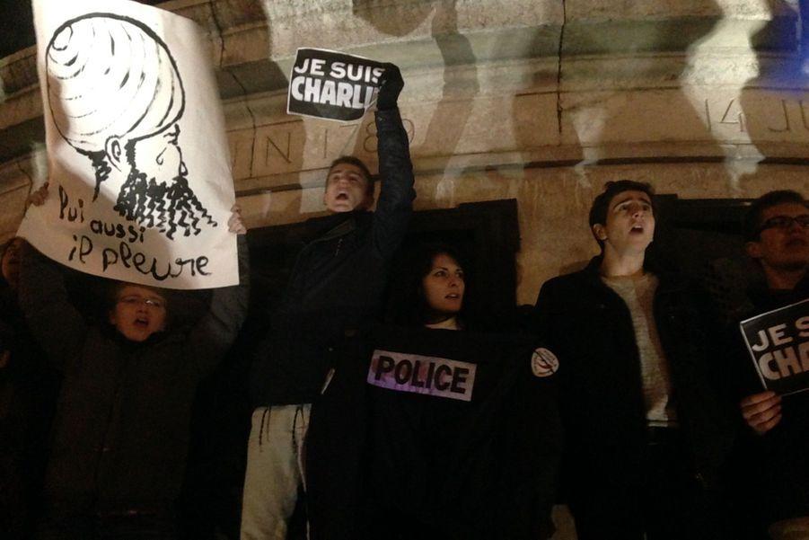 Parmi les manifestants rassemblés sur la statue, au centre de la place de la République, cette femme, apparemment une policière, tend une veste d'un agent de police qui semble maculée de sang.