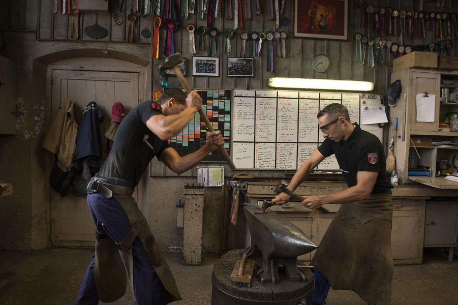 L'adjudant chef de la forge Romain V. martèle un fer à cheval à fer chaud avec l'aide du garde Mathieu T., le30 juin 2020 au Quartier Carnot à Vincennes.