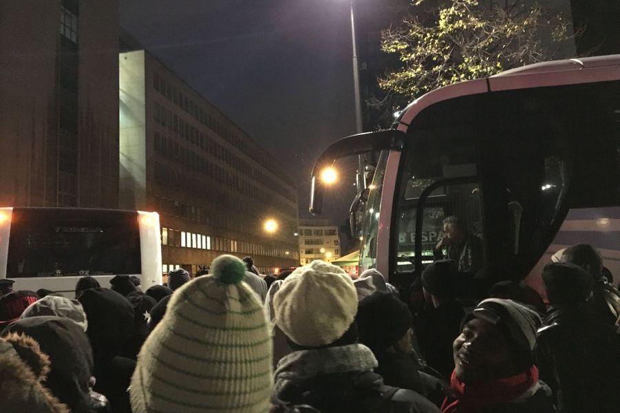 Les migrants se dirigent vers les cars à bord desquels ils seront conduits vers des centres d'hébergement.