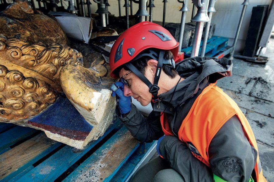 Sous le chapiteau installé sur le parvis. Lise Leroux, géologue du Laboratoire de recherche des Monuments historiques (LRMH), analyse l'état d'une sculpture.