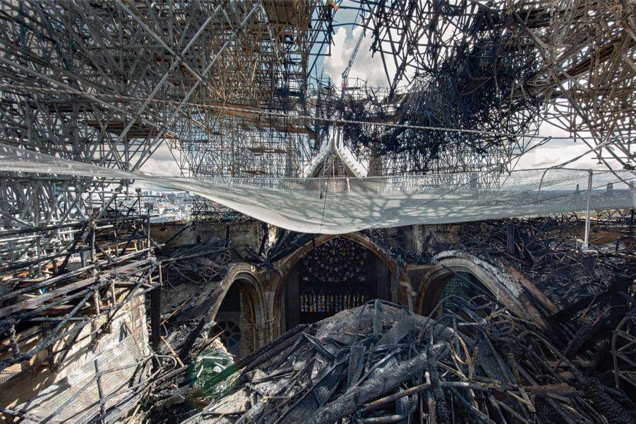 AU NIVEAU DE LA « FORÊT » A la croisée de la nef et du transept (avec vue sur le pignon sud), à l'emplacement de la flèche. Destinée à être rénovée, elle était entourée d'un échafaudage en acier ignifugé qui va être démonté pièce par pièce. Dans le fond, la Rose sud, édifiée en 1260, a résisté aux flammes.