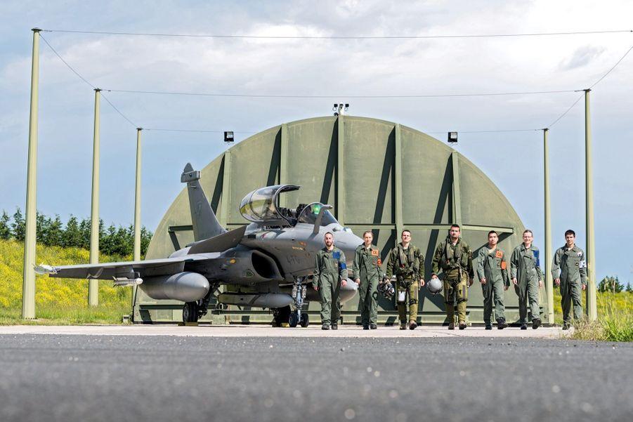 Devant une alvéole de la zone d'alerte de l'escadron de chasse 1/4 Gascogne, un Rafale B et son équipage au complet : en tenue de vol, le pilote (au centre avec le casque) et le navigateur officier systèmes d'armes (Nosa). Ils sont entourés par les chefs avions (brassard orange). Ensuite, par les mécaniciens. A droite, le gendarme de la sécurité et des armements nucléaires.