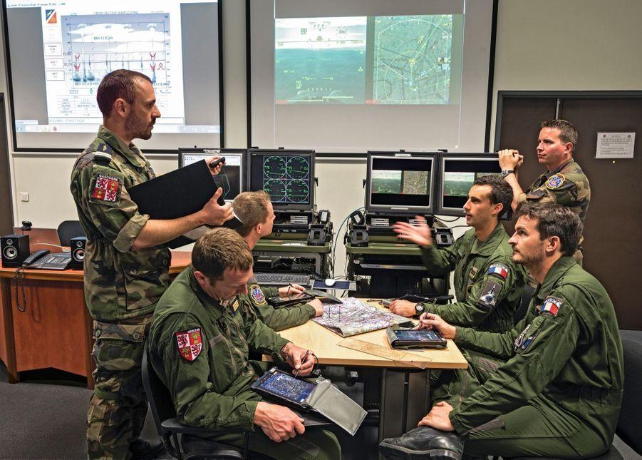 Séance de briefing avant le vol. Assis, deux équipages de l'escadron 1/4 Gascogne encadrés par un officier (à g.) et un sous-officier renseignement (à dr.). Ils décrivent la situation et les menaces qu'ils pourront rencontrer. Derrière, les écrans qui permettront la restitution de leur vol, seconde par seconde.