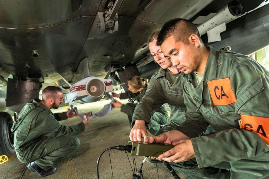 Sous un Rafale B, au premier plan, deux chefs avions se chargent des dernières vérifications. Derrière eux, deux mécaniciens enlèvent le cache de l'arme nucléaire avant le décollage. Chaque geste est surveillé et répond à des consignes écrites.