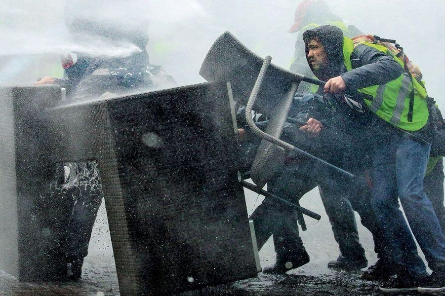 Une chaise, dérisoire défense contre la violence d'un canon à eau