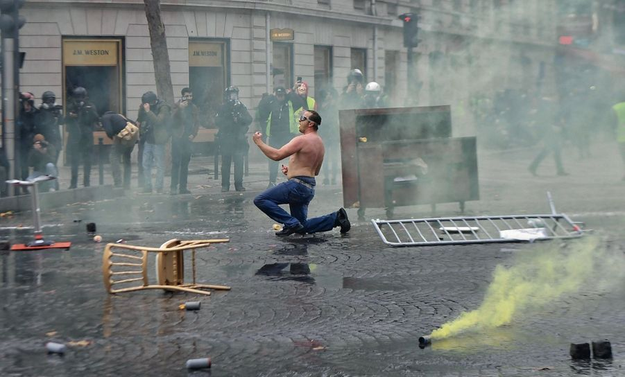 Torse nu avec des lunettes de piscine, un manifestant affronte seul le canon à eau.