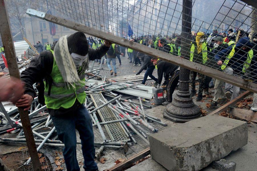 Construction d'une barricade avec des éléments d'échafaudages près de la place de l'Etoile.
