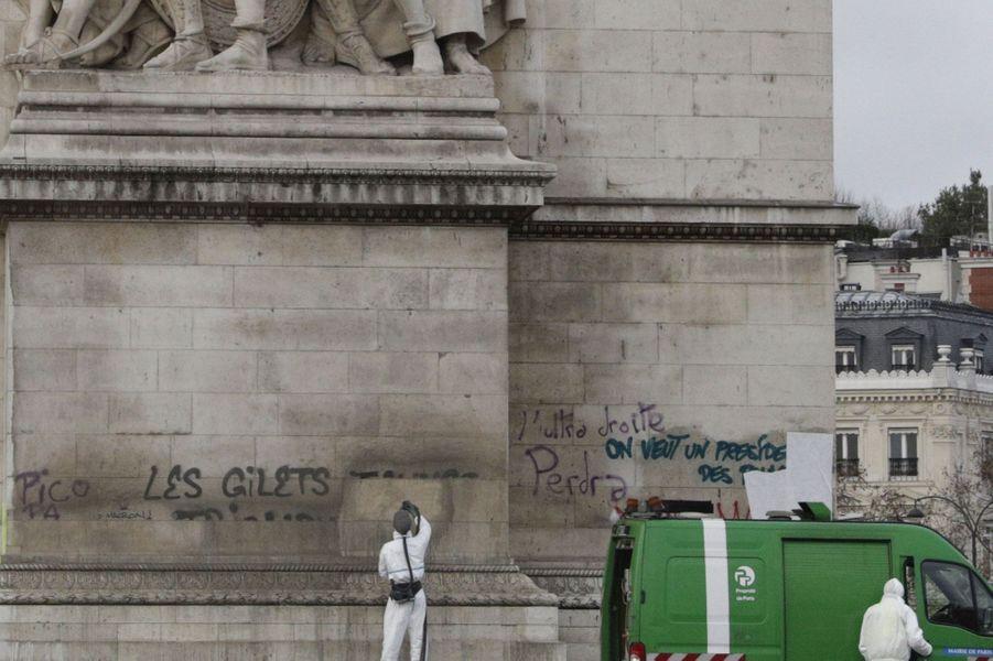 Des employés municipaux nettoient les inscriptions sur l'Arc de Triomphe, dimanche