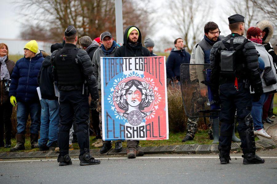 Un manifestant tient une pancarte inspirée par l'œuvre d'Obey qui figure dans le bureau d'Emmanuel Macron, mardi près de Grand Bourgtheroulde, dans l'Eure.