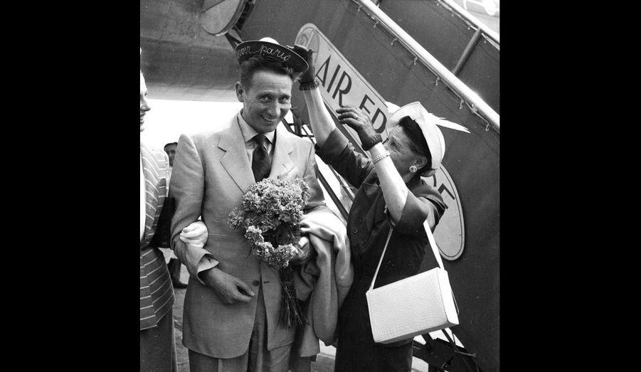 Deux ans qu'il n'avait pas posé les pieds sur le sol français à l'aéroport Paris-Orly. Charles Trenet est de retour après son long périple aux Etats-Unis. A la gauche du chanteur, sa mère lui a réservé une surprise : le «bachi» des marins avec l'inscription « Revoir Paris ».