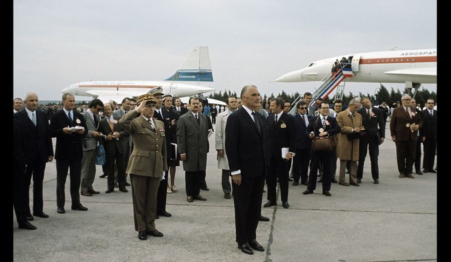 Vol expérimental du Concorde en arrière-plan à l'aéroport Paris-Orly, salué par le président Georges Pompidou, sous l'oeil attentif de la presse.