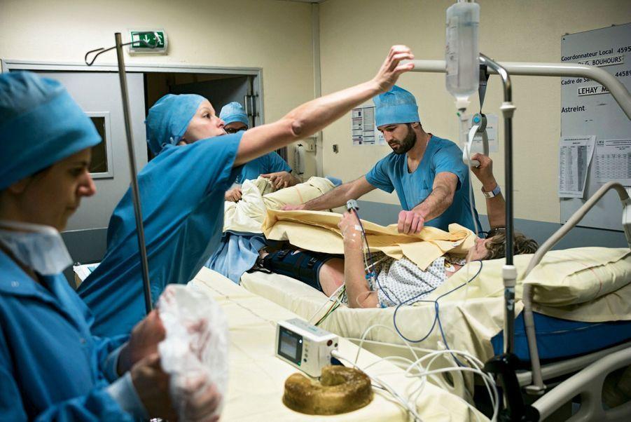 Dans le sas entre les urgences et le bloc, Sophie, 53 ans, est conduite en salle d'opération pour une luxation du genou gauche, le 7 mars