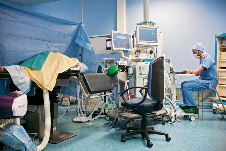 Arnaud, 42 ans, dans son « cockpit ». Deux moniteurs l'informent de la fréquence cardiaque et de la tension de son patient (à g.).