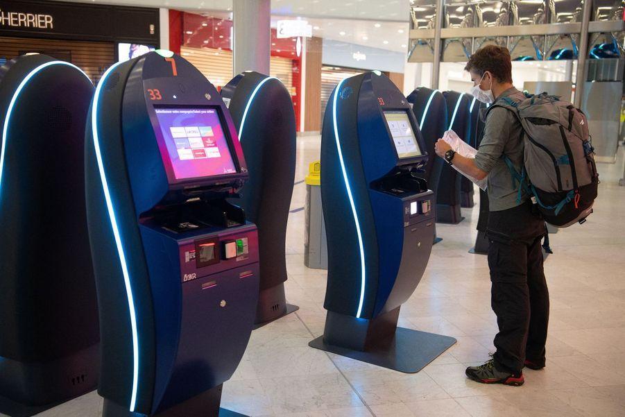 Un passager utilise une borne d'enregistrement en ligne dans le terminal 3, le seul ouvert pour l'instant.